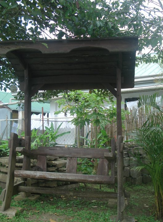Swing bench behind gazebo.